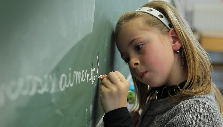 Une enfant écricant au tableau